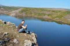 Ung man som tycker om sikten av en härlig sjö Arkivbild