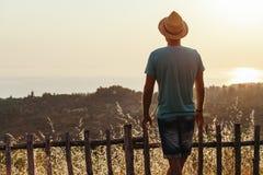 Ung man som tycker om solnedgång vid havet Royaltyfria Bilder