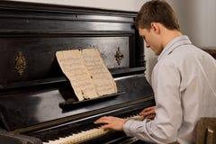 Ung man som tycker om spela en gammal melodi Arkivfoto