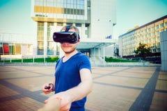 Ung man som tycker om virtuell verklighetexponeringsglas som rymmer handen av flickvännen på den moderna stadsbakgrunden Följ mig Royaltyfria Bilder