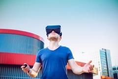 Ung man som tycker om virtuell verklighetexponeringsglashörlurar med mikrofon, eller anblickar som 3d utomhus står mot modern byg Royaltyfri Foto