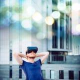 Ung man som tycker om virtuell verklighetexponeringsglashörlurar med mikrofon, eller anblickar som 3d ser upp och ut står mot mod Arkivbild