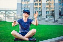 Ung man som tycker om virtuell verklighetexponeringsglashörlurar med mikrofon, eller anblickar som 3d utomhus sitter på den gröna Royaltyfri Bild