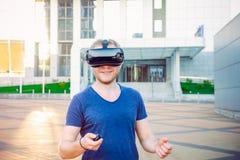 Ung man som tycker om virtuell verklighetexponeringsglashörlurar med mikrofon, eller anblickar som 3d utomhus står mot modern byg Arkivbild
