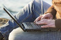 Ung man som utanför använder hans bärbar dator royaltyfri fotografi