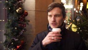 Ung man som utomhus dricker kaffe på stadsgatan på natten lager videofilmer