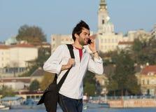 Ung man som utomhus går med mobiltelefonen Arkivbilder