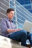 Ung man som utomhus kopplar av med bärbara datorn Arkivfoto