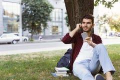 Ung man som utomhus lyssnar till musik på gräset Royaltyfria Foton
