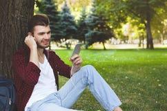 Ung man som utomhus lyssnar till musik på gräset Royaltyfri Fotografi