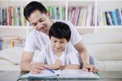 Ung man som vägleder hans son för att studera arkivfoto
