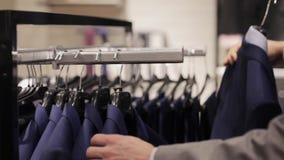 Ung man som väljer kläder i klädlager arkivfilmer