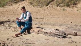 Ung man som väntar på hans datum på kusten, strand stock video