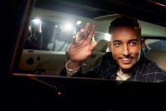 Ung man som vinkar från baksidan av en drivande limo för chaufför arkivfoton