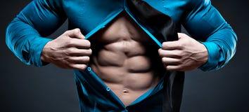Ung man som visar hans buk- muskler royaltyfri fotografi