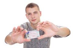 Ung man som visar hans körkort Arkivfoton