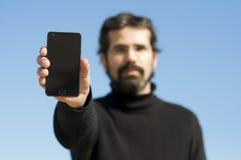 Ung man som visar hans mobiltelefon Arkivfoto
