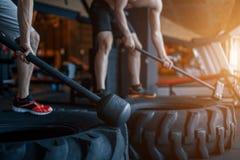 Ung man två med ett hammareslag på ett gummihjul i idrottshallen genomkörare Royaltyfria Foton