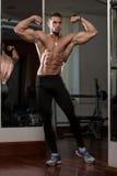 Ung man utförande Front Double Biceps Pose arkivbilder