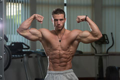 Ung man utförande Front Double Biceps Pose Arkivbild