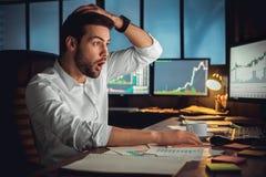 Ung manlig affärsman på begreppet för kontorsarbete som sitter se den chockade skärmen arkivbild