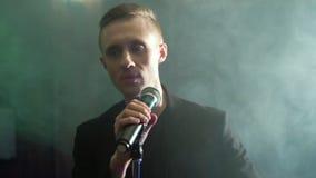 Ung manlig akt?r som sjunger i ett m?rkt r?kigt rum arkivfilmer