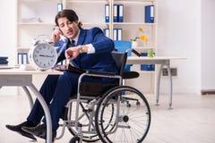 Ung manlig anst?lld i rullstolarbete i kontoret royaltyfria bilder