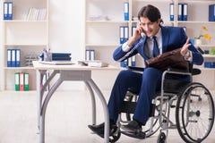 Ung manlig anst?lld i rullstolarbete i kontoret fotografering för bildbyråer