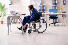 Ung manlig anst?lld i rullstolarbete i kontoret arkivbilder