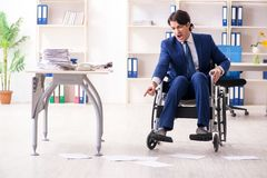Ung manlig anst?lld i rullstolarbete i kontoret arkivbild