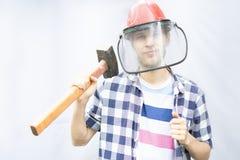 Ung manlig arbetare i den skyddande maskeringen som rymmer en hammare med kopieringsutrymme f arkivbild