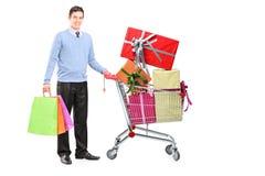 Ung manlig bredvid en shoppingvagn full av gåvor arkivbild