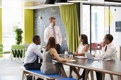 Ung manlig chef som tilltalar kollegor på det informella mötet arkivbild