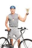Ung manlig cyklist som rymmer en trofé Arkivbild
