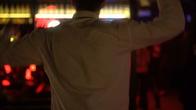 Ung manlig dans på diskostången som kopplar av i nattklubb på helg, baksidasikt stock video