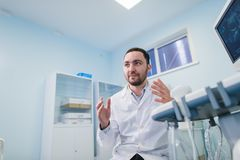 Ung manlig doktor som förklarar ultraljudsundersökning till gravida kvinnan i sjukhus royaltyfri foto