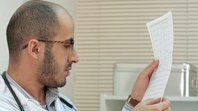 Ung manlig doktor som ser kardiogrammet fotografering för bildbyråer