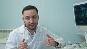 Ung manlig doktor som talar till kamerasammanträdet bredvid ultraljudscanningmaskinen lager videofilmer