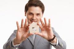 Ung manlig fastighetsmäklare för stående för begreppsdollaren för 100 bills det gjorda huset intecknar ut Fotografering för Bildbyråer