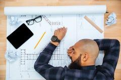 Ung manlig formgivare som ligger och sover på tabellen med ritningen Arkivfoton