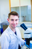 Ung manlig forskare med ett mikroskop som kontrollerar hans prövkopia Arkivfoto