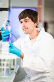 Ung manlig forskare som ut bär vetenskaplig forskning i en labb Royaltyfri Bild