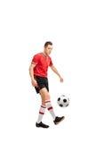Ung manlig fotbollsspelare som jonglerar en boll Royaltyfri Bild