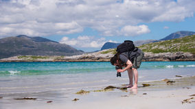 Ung manlig fotograf med dreadlocks på en solig vit sandstrand, royaltyfri foto