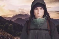 Ung manlig fotvandrare p? molnig landskapbakgrund som ser kameran Bekl?da besk?dar aktiv livsstil och turism royaltyfri bild