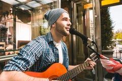 Ung manlig gitarrist som trycker på anda nära stång arkivfoto