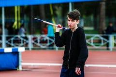Ung manlig idrottsman nen omkring som kastar kastspjutet Arkivfoton