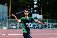 Ung manlig idrottsman nen omkring som kastar kastspjutet Royaltyfri Foto