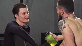 Ung manlig idrottsman nen som talar till hans vän på idrottshallen lager videofilmer