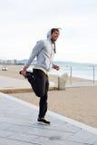 Ung manlig idrottsman nen som värmer upp efter en intensiv spring på stranden arkivbilder